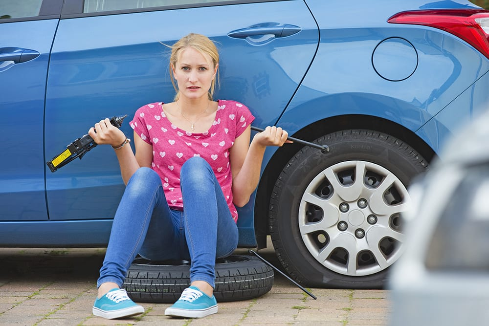 woman change car tyre
