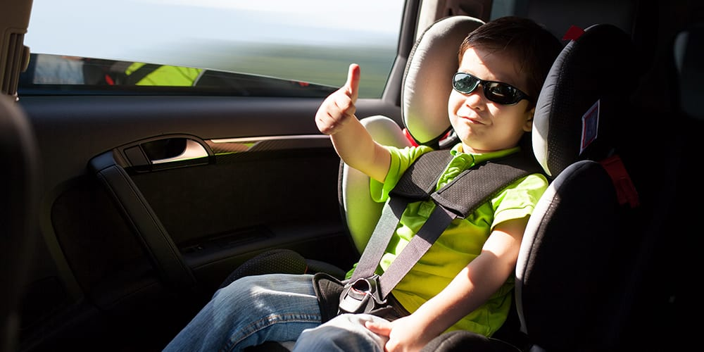 happy kid in car - summer driving tips