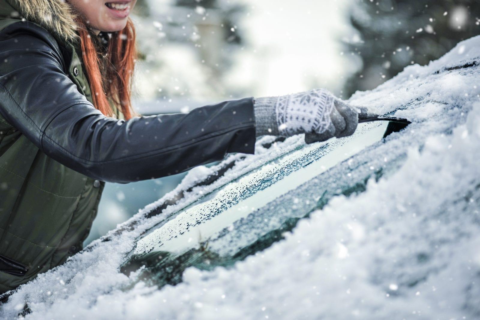 Woman de-icing car